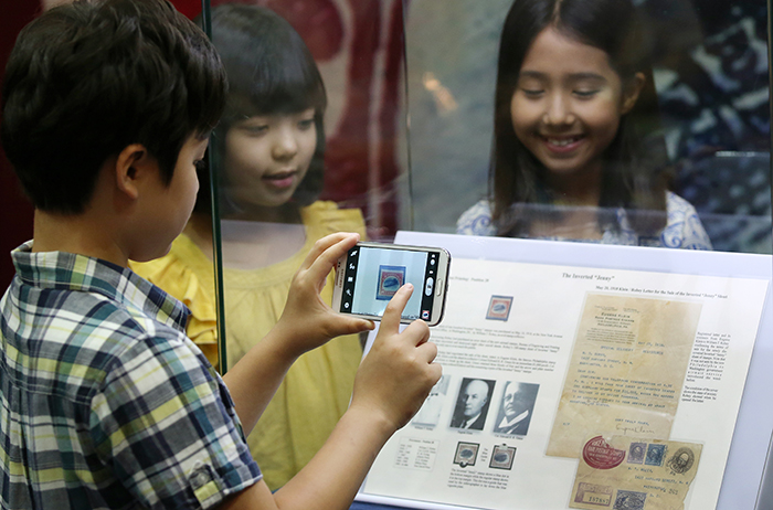 A rare stamp, the Inverted Jenny, is a U.S. stamp of a Curtiss JN-4 airplane. It attracts the attention of many young people visiting the PHILAKOREA 2014 World Stamp Exhibition. (photo: Jeon Han)